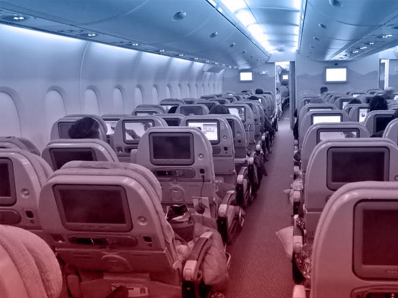 interior de avião com monitores nos acentos
